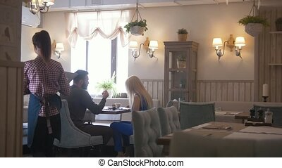 Young couple takes the menu to make an order at the cafe