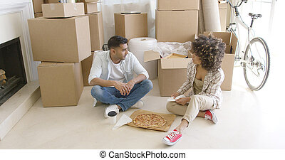 Young couple taking a break from moving house