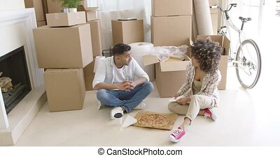 Young couple taking a break from moving house sitting on the...