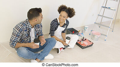 Young couple taking a break from redecorating