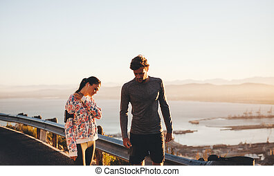 Young couple taking a break from running session