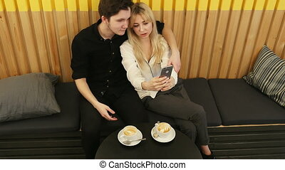 Young couple taking a photo of themselves in a cafe