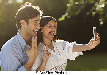 Young couple taking a selfie in the park - Beautiful young...