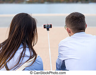 Young couple taking a selfie with smartphone on the stick.