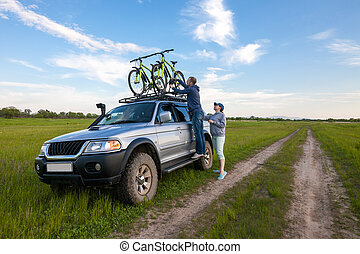 Young couple taking off their bicycles from roof rack