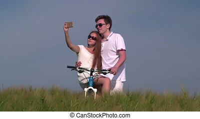 Young couple taking photo with smart phone making selfie