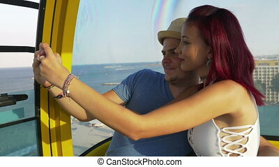 Young couple taking selfie in cable car