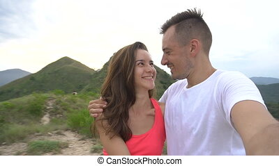 Young couple taking selfie, laughing and go round in the mountains with beautiful aerial city view, enjoy the nature and carefree life