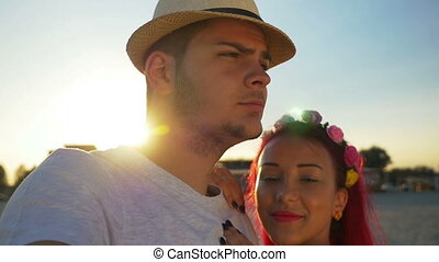 Young couple taking selfie on the beach at sunset