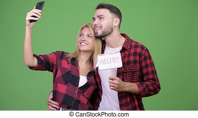 Young couple taking selfie while holding paper sign together...