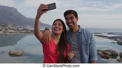 Young couple taking selfies - Front view of a mixed race ...
