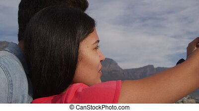 Young couple taking selfies - Side view close up of a mixed ...