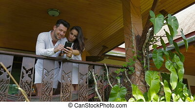 Young Couple Talk Holding Cell Smart Phone On Balcony In...