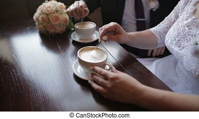 Young couple talking and drinking coffee during breakfast at cafe. They mixing sugar in cappuccino.