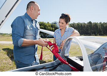 young couple talking next to lightweight airplane