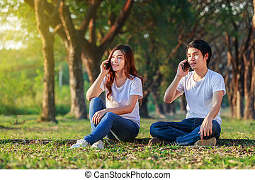 couple talking on mobile phone in the park
