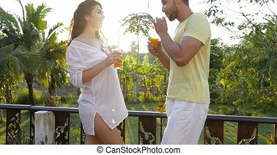 Young Couple Talking On Terrace At Sunset Drinking Orange...