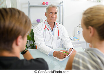 Young couple talking to senior doctor