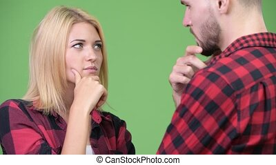 Young couple thinking while looking at each other - Studio...