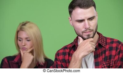 Young couple thinking while looking down together - Studio...