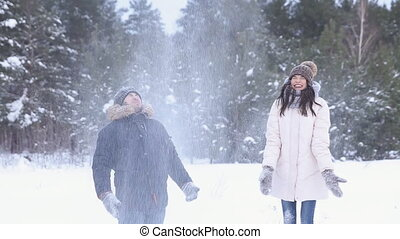 Young Couple throwing a snowballs outdoors.