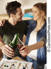Young couple toasting beer bottles