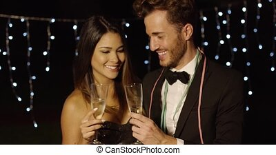 Young couple toasting the New Year with champagne smiling...