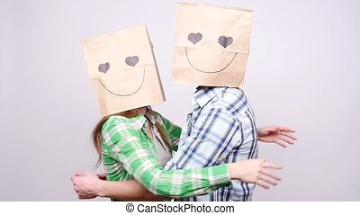 Couple together man and woman with bags over heads on gray...