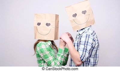 Couple together man and woman with bags over heads on gray background