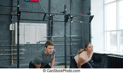 Young couple training in gym weightlifting squatting with ...