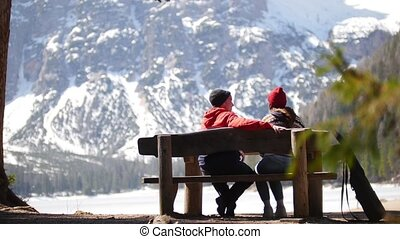 Young couple traveling. Sitting on a bench and talking