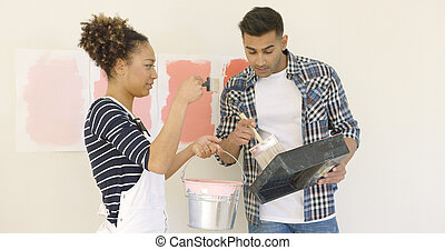 Young couple trying out different shades of paint to...