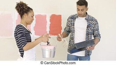 Young couple trying out different shades of paint