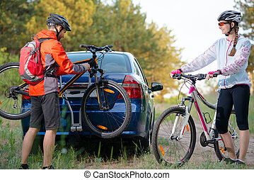 Young Couple Unmounting Mountain Bikes from Bike Rack on the Car. Adventure and Family Travel Concept.