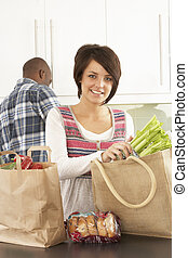 Young Couple Unpacking Shopping In Modern Kitchen