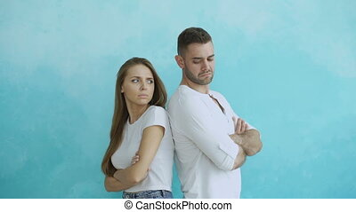 Young couple upset and angry each other standing rear on blue background