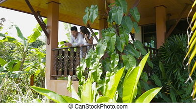 Young Couple Use Cell Smart Phone Talking Stand On Balcony In Hotel, Happy Smiling Man And Woman Surfing Internet Together