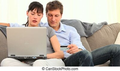 Young couple using a credit card on internet