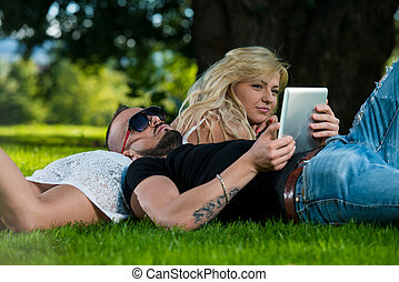Young Couple Using A Digital Tablet In The Park - Beautiful ...