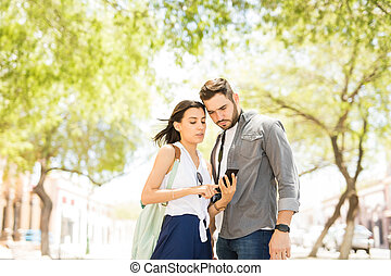 Young couple using a smartphone for navigation during...