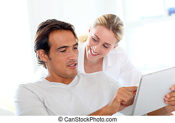 Young couple using electronic tablet at home