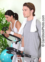 Young couple using gym equipment