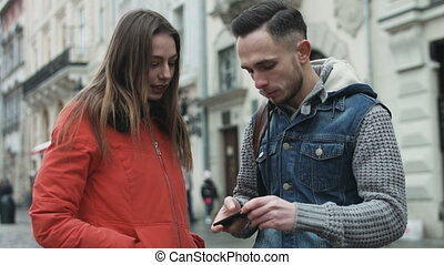 Young couple using mobile device outdoors in the european city center.