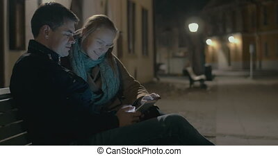 Young couple using pad on the street bench