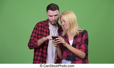 Young couple using phone together - Studio shot of young...