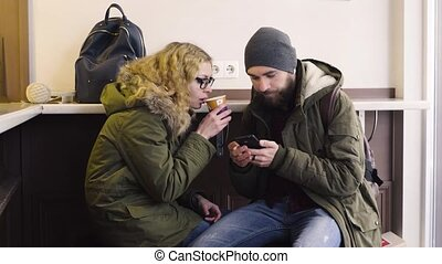 Young couple using smartphone sitting in cafe in city