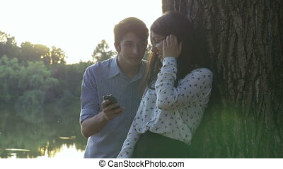 Young couple using the smartphone in the park