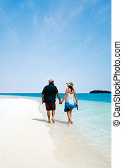 Young couple, male and female walks on the white sand of Aitutaki Lagoon, Cook Islands