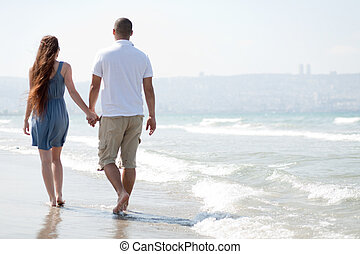 young couple walk at the beach
