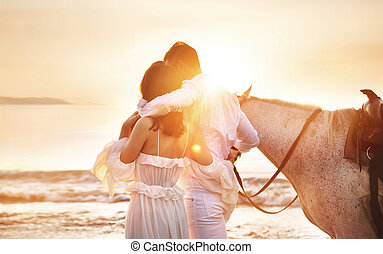 Young couple walking a majestic horse - seaside landscape